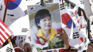 A supporter of South Korean President Park Geun-hye holds up her portrait during a rally opposing her impeachment in Seoul, South Korea, Friday, 10 March 2017