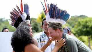 Prince Harry is presented with a headdress by dancers in Sumara, Guyana, during his tour of the Caribbean