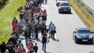 Migrants walk on a road in Denmark