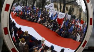 People holding a giant Polish national flag are reflected in a mirror as they take part in a march demanding their government to respect the country's constitution in Warsaw, Poland (12 March 2016)