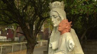 A view of the white statue of Mary and baby Jesus with the orange replacement head