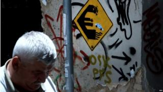 A man passes by a graffiti showing a euro sign and a car in the colours of Greece jumping off on the wall of an old house in Athens, Greece, on 24 June 2015