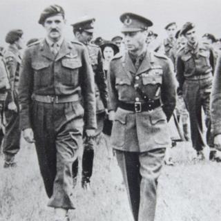 Princess Elizabeth is seen behind King George VI