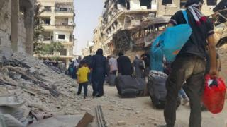 Residents of Darayya, in Syria, carry belongings as they prepare to evacuate