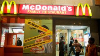 A security guard opens the door for customers at McDonalds in Khan Market on February 24, 2009 in New Delhi, India.