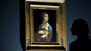 """a woman posing for pictures beside a painting entitled """"Portrait of Cecilia Gallerani"""" (The Lady with an Ermine) by Italian artist Leonardo da Vinci, London"""