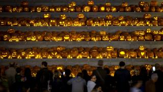 Hundreds of jack-o'-lanterns sat on some stone steps as people look and take photographs.