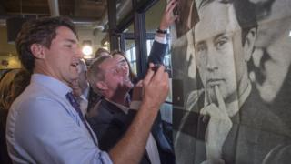 Justin Trudeau signs a photo of his father during an October campaign stop