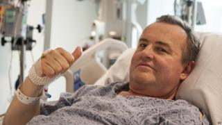 Mr Manning gives a thumbs-up while resting in his hospital bed