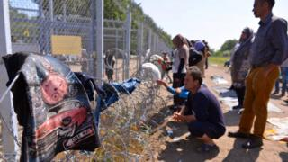 Migrants stand by the border fence in a makeshift camp near the Horgos border crossing into Hungary, near Horgos, Serbia, on 27 May