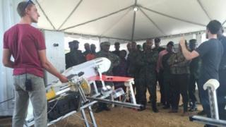Les concepteurs des drones présentent les engins à des soldats rwandais.