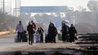 Civilians leave the frontline neighbourhood of Dahiyet al-Assad in western Aleppo