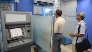 Indian customers update their passbooks at a State Bank of India ATM in Siliguri on November 21, 2016.