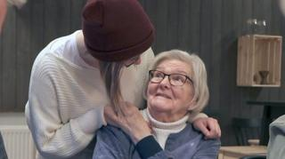 A young and old resident embrace.