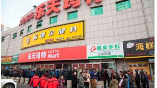 Chinese people stand outside a closed Lotte store in Jilin, in Jilin province, China, on March 9, 2017.