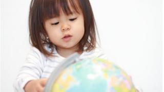 Menina olhando globo terrestre