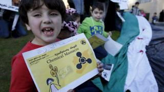 A child holds up a poster saying Syrians would never forget the August 2013 chemical weapons attack in Damascus, outside the UN headquarters in Beirut (26 December 2015)