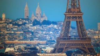 The Eiffel Tower is seen in front of the Sacre Coeur Basilica on Montmartre