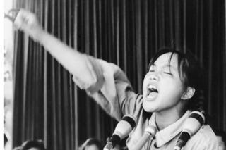 Close up image of a young woman calling out to fellow Red Guards from a platform in Beijing's Tiananmen Square on 10 August 1966