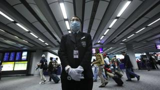 A health worker stands by ready to ask passengers to remove head gear prior to temperature screening on April 27, 2009 at the international airport in Hong Kong