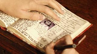 model of Anne Frank writing her diary