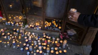 An Israeli man stops to light a candle at a memorial in the entrance of the cafe in Tel Aviv, Israel, 02 January 2016