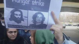 Woman holds poster with picture of Iranian activist Arash Sadeghi
