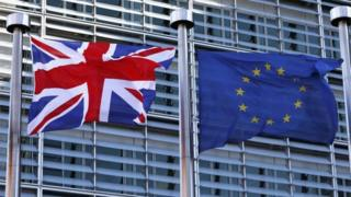 A Union Jack flag flutters next to European Union flags