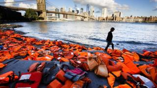 A woman walks past hundreds of refugee life jackets collected from the beaches of Chios, Greece, on the edge of the East River, to call attention to the refugee crisis in Brooklyn, New York, USA, 16 September 2016