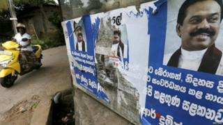 A woman rides her bike past election posters of Sri Lanka's former Sri Lankan president Mahinda Rajapaksa for the upcoming general election