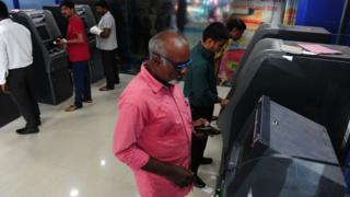 File photo of people withdrawing money