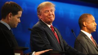 Donald Trump smirks next to Ben Carson and Marco Rubio.