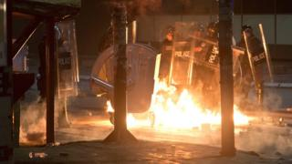 Petrol bomb is thrown at police officers in Kosovo capital Pristina as clashes broke out after the arrest of a prominent opposition politician Albin Kurti on Monday, Oct. 12, 2015.