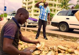 A man cutting coconuts on a street in Libreville, Gabon - Sunday 29 January 2017