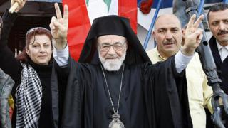 Hilarion Capucci (C) makes victory signs before setting sail on Gaza-bound aid ship (2 February 2009) from northern Lebanese city of Tripoli