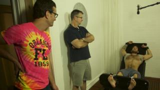 Un hombre sin camisa y descalzo está acostado en una silla rodeado de otros dos hombres que lo ven.