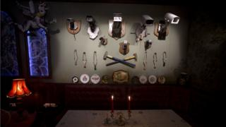 """A wall decorated with security cameras and slingshots is seen in the bar area of the """"The Walled Off Hotel"""" and the Israeli security barrier in the West Bank city of Bethlehem, Friday, March 3, 2017."""