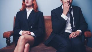 Mujer con las piernas cruzadas y hombre mordiéndose las uñas, en espera de una entrevista de trabajo.