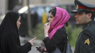 A member of Iran's morality patrols (l) in Tehran admonishes a young woman (c) for her dress in April 2007.