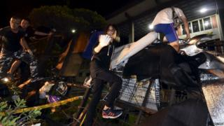Protesters climb over a barricade to enter the Ministry of Education in Taipei, Taiwan, 31 July 2015