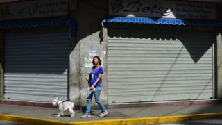 A woman passes by closed stores in Caracas, on October 28, 2016