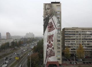 Geleneksel Ukrayna kıyafetleriyle çizilen bu kız resmi Kiev'deki Sovyet döneminden kalma 18 katlı bir apartmanın kenarına yapıldı.
