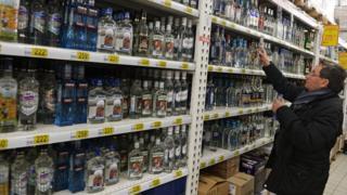 Посетитель выбирает алкогольный напиток в московском магазине