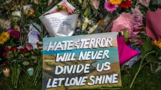 "Banner reading ""Hate and terror will never divide us"" laid upon flowers"