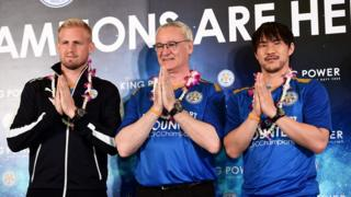 "From left: player Kasper Schmeichel, manager Claudio Ranieri, and player Shinji Okazaki put their hands together in a traditional Thai ""wai"" greeting gesture, on a press stage in Bangkok's main international airport (18 May 2016)"