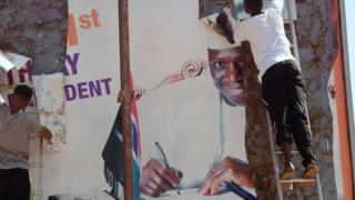 Workers remove an electoral poster of Gambia's President Yahya Jammeh, in a street of Bijilo, on 4 December 2016 after he initially accepted defeat