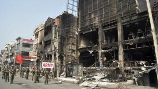Indian soldiers conduct a flag march past damaged buildings at Rohtak (20 February 2016)