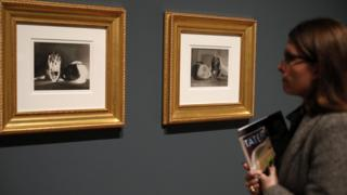 Woman looks at Man Ray's photographs Noire et Blanche at The Radical Eye exhibition