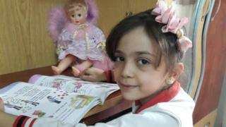 Bana Alabed, seated at a desk with a book and doll, from her Twitter account