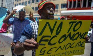 A protester holds a sign during a demonstration by opposition parties against the introduction of bond notes as a currency in Harare, Zimbabwe 30 November 2016